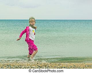 Beautiful girl having fun playing in the cold sea.