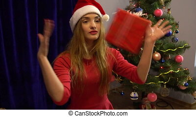 beautiful girl having fun with christmas gift and showing thumbs up
