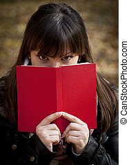 Beautiful girl hiding behind the book