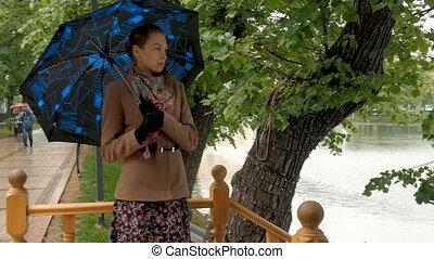 Beautiful girl hiding from the rain under an umbrella