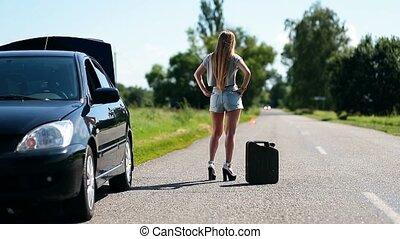 Beautiful girl hitchhiking on rural road back view