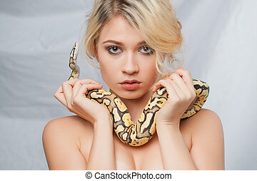 Beautiful girl holding a python, which wraps around her body...