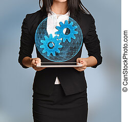 Beautiful girl holding a tablet with digital network globe and gear icon