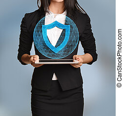 Beautiful girl holding a tablet with digital network globe and shield icon