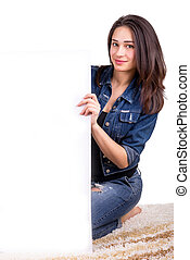 beautiful girl holding a white placard sitting on the carpet