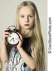 Beautiful girl holding alarm clock
