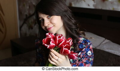 Beautiful girl holding flowers, looking at the camera, smiling, flirting.