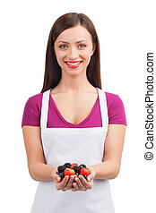 beautiful girl holding pile of fruits. closeup of brunette wearing apron and smiling