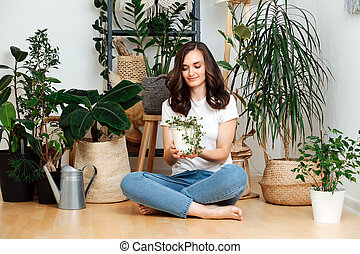 Beautiful girl holds a pot with a plant