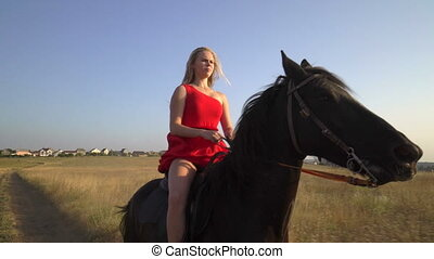 Beautiful girl horseback rider in red dress riding horse across dry grass field