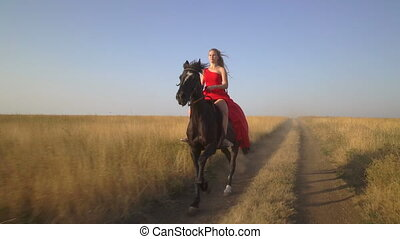 Beautiful girl horseback rider in red dress riding horse across dry grass field.