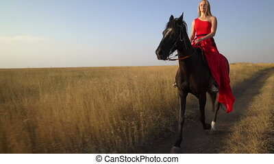 Beautiful girl horseback rider in red dress riding horse...