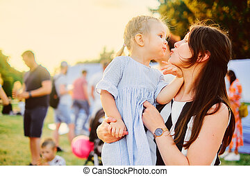 beautiful girl hugs with her three year old daughter on a park background