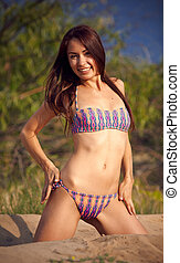 Beautiful girl in a bikini on a background a pine-wood.