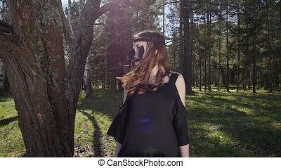 Beautiful girl in a black dress walks in the woods