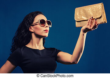 beautiful girl in a black dress with golden clutch