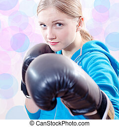 beautiful girl in a blue sportswear and gloves for boxing or kick-boxing closeup portrait on light bokeh background