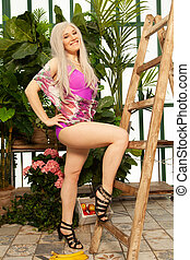 beautiful girl in a bright pink swimsuit in the greenhouse poses among the plants and enjoys the clean air and harmony from communicating with nature