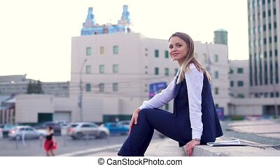 Beautiful girl in a business suit in the city center, sitting on the stairs, looking at the camera.