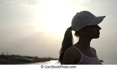 beautiful girl in a cap at sunset 4k