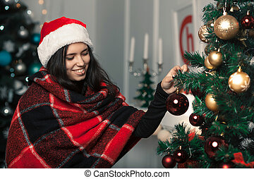 Beautiful girl in a Christmas room dress up a Christmas tree with Christmas toys