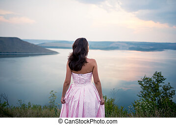 girl in a dress looks at the horizon of the river