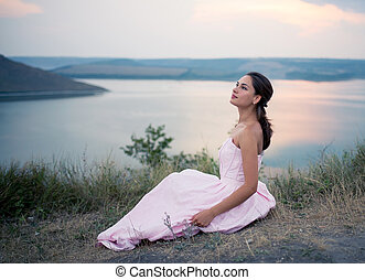 girl in a dress sitting on a rock by the river