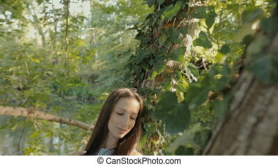 Beautiful girl in a dress stands near the tree in the forest
