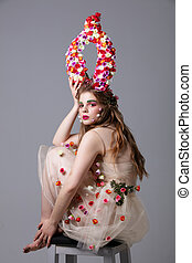 Beautiful girl in a fabulous look with flower horns sits on a chair. Maleficent. Spring or summer beauty. Woman in the image of a flower.