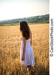girl in a field looking at sunset