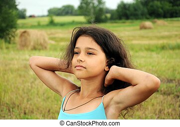 Beautiful girl in a field on a background of straw