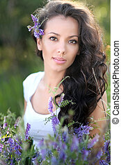 beautiful girl in a field with blooming flowers