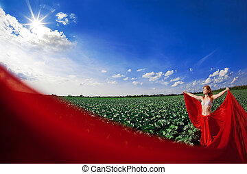 Beautiful girl in a field with red fabric