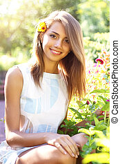 Beautiful girl in a flowered garden