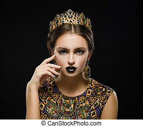 Beautiful girl in a golden crown and earrings on a dark background
