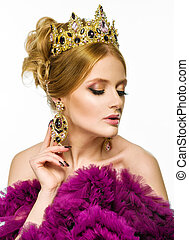 Beautiful girl in a golden crown and earrings on a white background