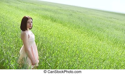 Beautiful girl in a green field lifestyle with wheat. Grass woman field nature