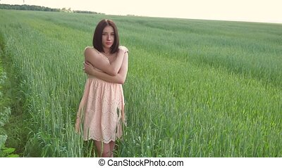 Beautiful girl in a green field with wheat. Grass woman field lifestyle nature