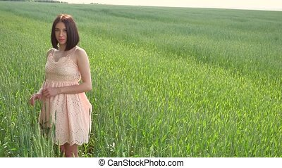 Beautiful girl in a green field with wheat. Grass woman field nature lifestyle