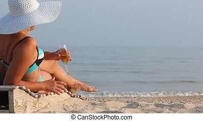 Beautiful girl in a hat on a lounger drinking wine
