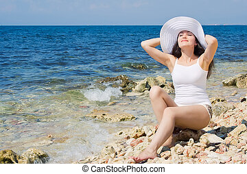 Beautiful girl in a hat on the beach