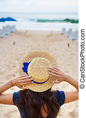 Beautiful girl in a hat sits on a beach.