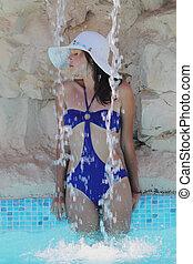 beautiful girl in a hat sunbathes