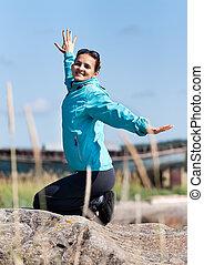 Beautiful girl in a jacket kneeling on a rock