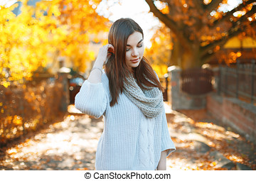 Beautiful girl in a knitted sweater on the background of a beautiful autumn park