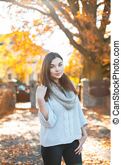 Beautiful girl in a light knit sweater on the background of autumn foliage