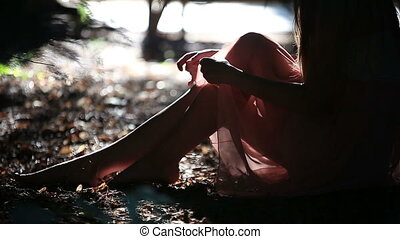 Beautiful Girl in a Light Pink Dress Resting in a Shadow of a Tree in the Park on a Sunny Summer Day