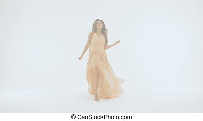 Beautiful girl in a long dress, she emotionally sings, on a white background. slow motion
