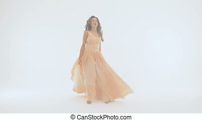 Beautiful girl in a long dress, she emotionally sings, on a white background.