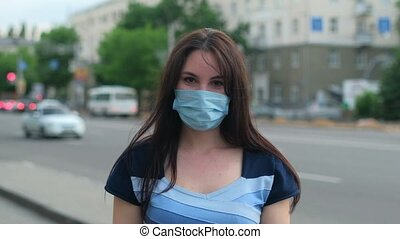 Beautiful girl in mask looks at the camera on the street. Slow motion